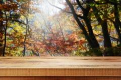 木桌和迷离秋天背景 库存图片