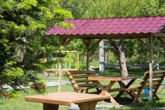 木桌和长凳与一个机盖在露天 免版税图库摄影