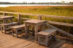 木桌和长凳在湖 免版税库存照片