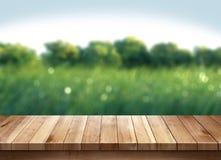 木桌和绿草被弄脏的背景 免版税图库摄影