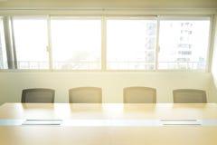 木桌在会议室从窗口的白板阳光下 免版税库存照片