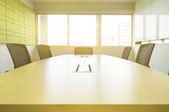 木桌在有减音材料阳光的会议室从窗口 免版税库存图片
