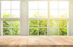 木桌柜台上面在迷离窗口视图庭院背景的 免版税库存照片
