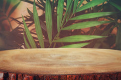 木桌的图象在前面热带绿色花卉背景中 对产品显示和介绍 免版税库存图片
