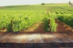 木桌的图象在葡萄园风景前面的 免版税库存照片