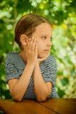 木桌的小美丽的女孩 免版税库存照片