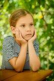 木桌的小美丽的女孩 图库摄影