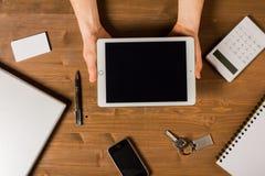 木桌面与人手和片剂 免版税图库摄影