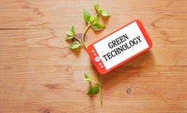 木桌面顶视图有植物和巧妙的电话的 绿色通讯技术概念 图库摄影