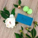 木桌顶视图与笔记本、绿色macarons和花的 平的拉特,看法从上面 库存照片