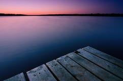 木桥和美好的微明在河在夏天 免版税图库摄影