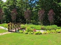 木桥在一个五颜六色的庭院里 库存图片