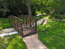 木桥在一个五颜六色的庭院里 免版税库存图片