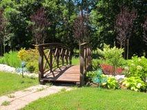 木桥在一个五颜六色的庭院里 免版税图库摄影