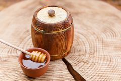 木桶用新鲜的蜂蜜和蜂蜜匙子在黏土碗在一把木锯 纬向条花 免版税库存图片