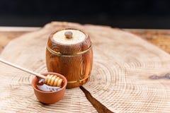 木桶用新鲜的蜂蜜和蜂蜜匙子在黏土碗在一把织地不很细木锯 纬向条花 免版税库存图片