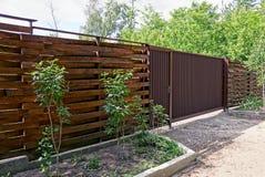 木棕色篱芭和闭合的门在街道上在路 库存图片