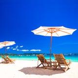 木椅子和伞在白色沙子靠岸 免版税库存图片