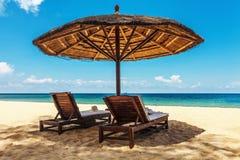 木椅子和伞在白色沙子靠岸 免版税库存照片