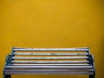 木椅子和黄色墙壁 库存照片