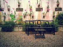 木椅子在一个自然地可爱的庭院里 免版税库存图片