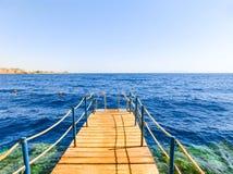 木楼梯在海滩的水中在礁石在Sharm El谢赫,埃及 免版税库存照片