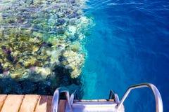 木楼梯在海滩的水中在礁石在Sharm El谢赫,埃及 图库摄影