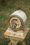木橡木桶酒,与金属起重机的啤酒。卖在市场。 免版税库存图片