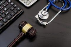 木法官惊堂木、计算器和听诊器在桌上 黑背景,医疗事故, a的概念 图库摄影