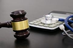 木法官惊堂木、计算器和听诊器在桌上 黑背景,医疗事故, a的概念 免版税图库摄影