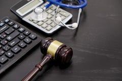 木法官惊堂木、计算器和听诊器在桌上 黑背景,医疗事故, a的概念 库存图片