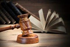 木法官惊堂木和老法律书籍在木背景 免版税库存照片