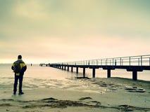 木海码头的人游人 与梯度阳光的冷的无风早晨 平稳的水 库存照片