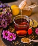 从木浸染工的滴下的甜蜂蜜在茶 免版税库存照片