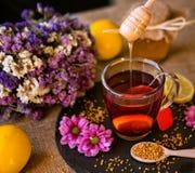 从木浸染工的水滴蜂蜜在茶 库存照片