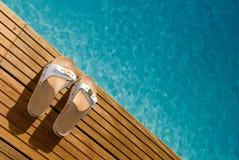 木游泳池边的凉鞋 图库摄影