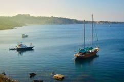 木游艇和有些小船在日落的一个美丽的海海湾停住 Konnos海湾,塞浦路斯 免版税图库摄影