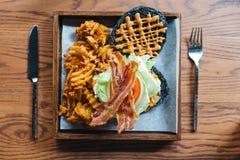 木炭芝士汉堡顶视图用嘎吱咬嚼的烟肉、圆白菜、葱、蕃茄、一千个海岛调味汁和奶蛋烘饼油炸物 免版税库存图片