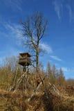木猎人高位子在有蓝天的森林里在背景中 免版税图库摄影