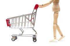 木玩偶和购物车在白色背景:浓缩的经济 免版税库存照片