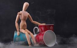 木玩偶坐杯子在雾被覆盖 库存照片