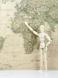 木玩偶用查寻在世界地图的手 免版税库存照片