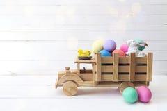 木玩具卡车用复活节彩蛋和一只兔子在后面 温泉 免版税库存图片
