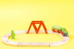 木玩具火车在黄色背景的轨道设置了 库存图片