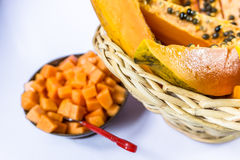 木瓜/番木瓜在藤茎水果篮在木背景 免版税库存图片