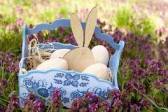 木的复活节彩蛋和在蓝色篮子的复活节兔子 库存照片