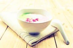 木盆蒂姆Krob,在糖浆和椰奶的被充塞的孛荠在木桌泰国点心 库存照片