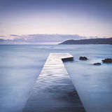 木码头、岩石和海有薄雾的日落的 免版税库存图片