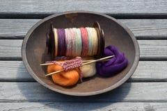 木碗充满手一个手纺车片盘转动了毛线、纤维和一个被编织的样品 图库摄影