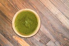 木碗在木纹理背景的绿茶粉末 库存照片